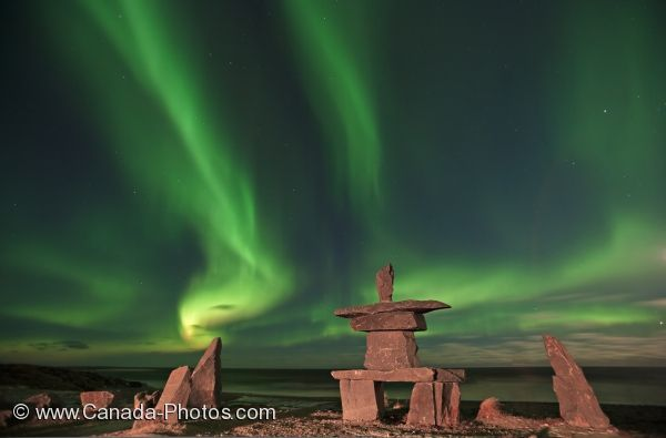 Picture of the Northern Lights creating a magical aura above an Inukshuk along the Hudson Bay in Churchill, Manitoba.