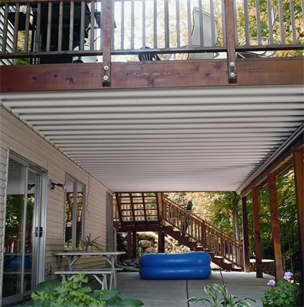 I love this covered deck as it resembles our set-up quite a bit. I like how it's got metal sheeting to make the bottom portion covered. I would put mosquito netting around it to be able to enclose it during the evenings.