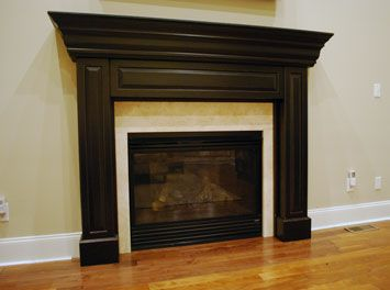 : The space is transformed with a new, custom fireplace mantel, complete with limestone surround. The finish is a chocolate black, glazed rub-off.