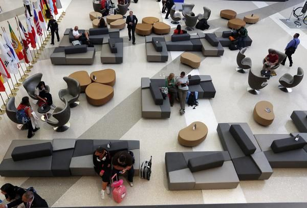 Travelers sit on stylized chairs and ottomans in a waiting area of the Tom Bradley International Terminal at Los Angeles International Airport.