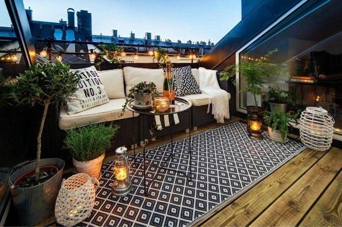 terrasse revêtement bois, taspis en noir et blanc à motifs géométriques, canapé noir avec coussin d'assise et coussins blancs, plantes, terrasse tropézienne
