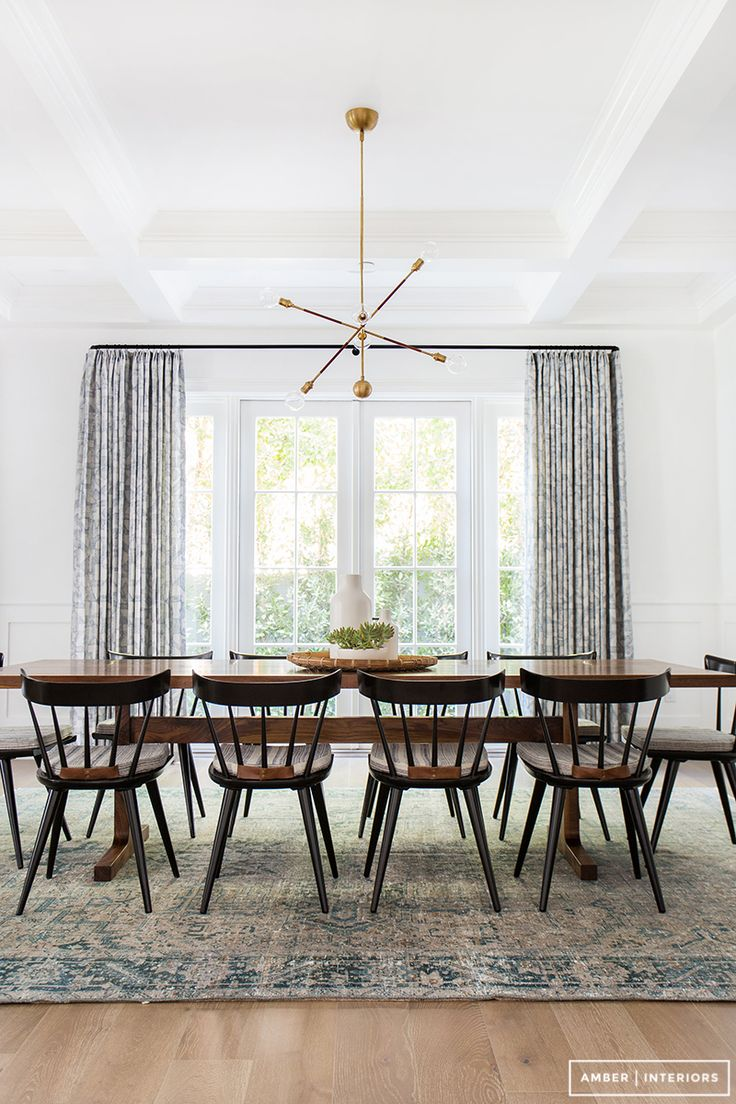A dining room simple yet fill with simple patterns from the rug and the curtains. Design inspiration