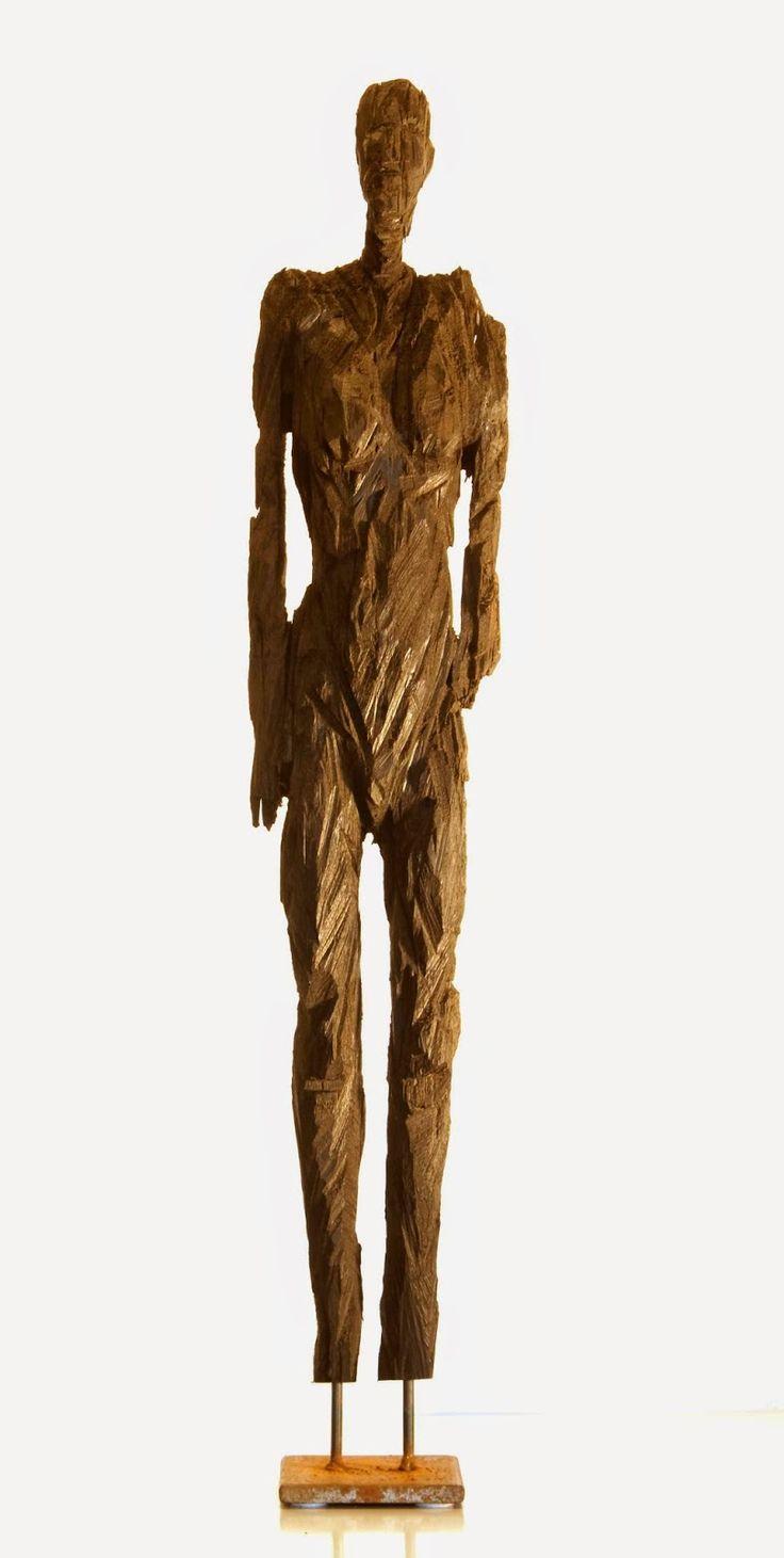 Georg Willms. Uit duizenden jaren oud moeraseik ontstaan bijzonder lange, archaïsch aandoende grote menselijke figuren, direct uit de stam gehouwen, gesneden of gezaagd