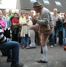 """Dorpsgek  Bartholomeus, de Middeleeuwse Dorpsgek. Hij praat, hij zingt en maakt muziek. Dit alles eenvoudig en puur, zoals bijvoorbeeld op zijn magisch klinkend instrument """"de hang"""". Is hij nu een filosoof. of toch een een halve troubadour..? In ieder geval weet hij waar het in het leven om draait.  http://www.oudhollandsentertainment.nl/Passanten.html#Nar"""