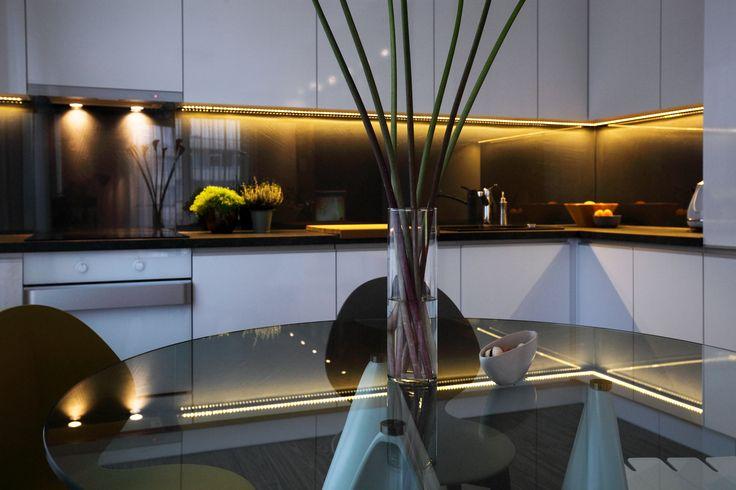 Nowoczesna minimalistyczna aranżacja kuchni w kolorach białym i czarnym. Obecny szklany stół jadalniany z kolorowymi krzesłami    Modern minimalist design of kitchen in white and black colors. There is a glass dining table with colorful chairs
