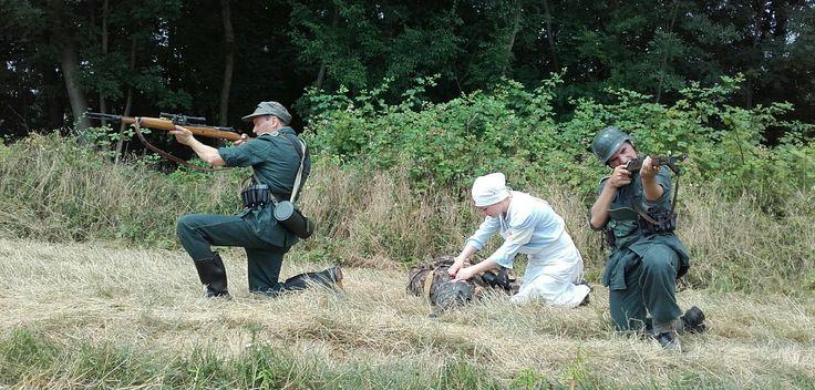 Rievocazione WW2  Scena di soccorso da parte di una crocerossina a un soldato tedesco caduto sul campo mentre altri due soldati coprono la zona TERNAVASSO 2016  - NORMANDIE 44