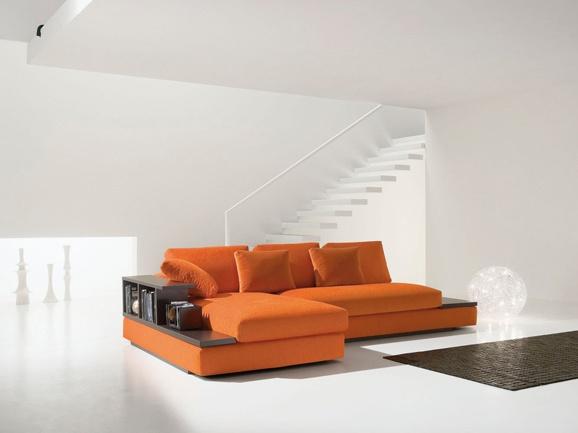 Divano angolare in tessuto arancione con piano d'appoggio e libreria in rovere moro.