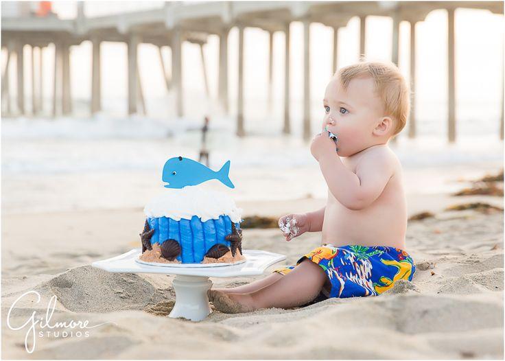 Foster's 1st birthday - Cake Smash Portrait Session - Huntington Beach Photographer, HB, Huntington Beach, Cali, CA, California, beach, ocean, sunset, cake smash, portrait session, first birthday, one year old, adorable, precious, darling, baby swim trunks, baby boy, checkered shirt, pier, HB pier, family, french's bakery, cake, ocean themed cake, blue whale cake, whale frosting, shells, yummy cake  GilmoreStudios.com