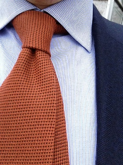 Navy jacket, white shirt with blue pinstripes, orange tie