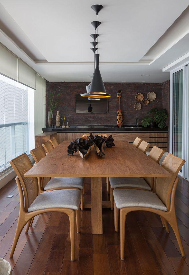 Decoração com influencias brasileiras com madeira e ambientes integrados. Na varanda mesa de madeira, cadeiras de madeira estofada, plantas e revestimento.