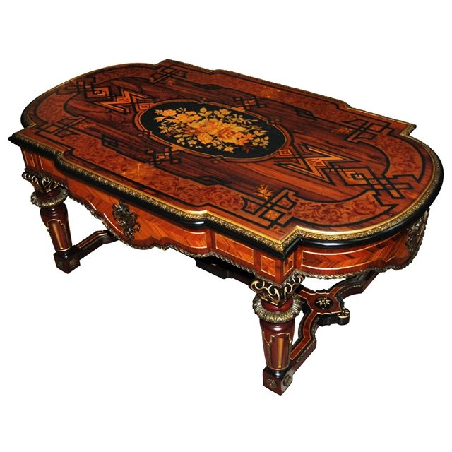 Beautiful antique Victorian Renaissance Revival inlaid coffee table executed in rosewood. This is a classic Pottier & Stymus piece. The inlay work features a beautiful floral motif that is highlighted by bronze trim and accents.