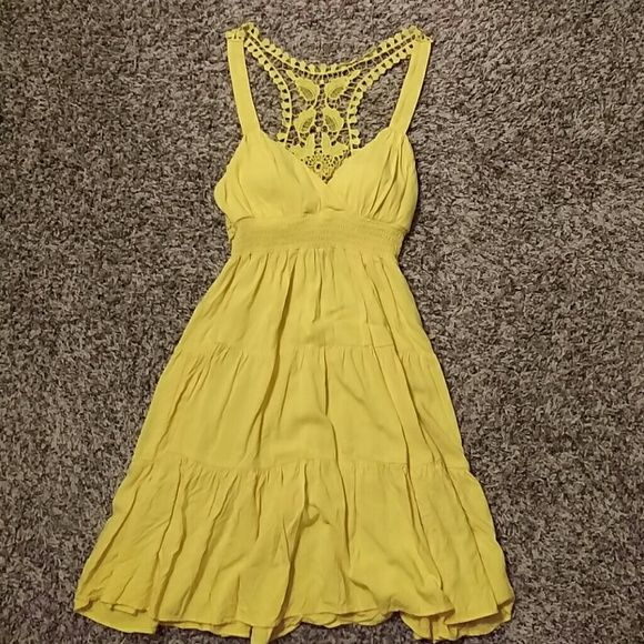 Yellow racerback sun dress Yellow racerback sun dress with pretty detailing in the back. The bust cups are lightly lined to give a nice shape. Ruffled, tiered skirt. Tag size is 7, but this dress fits as a small. City Triangles Dresses
