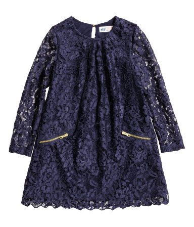 Donkerblauw. Een jurk van opengewerkt kant met lange mouwen en een ronde halsopening met platte plooien voor. De jurk heeft een splitje achter met een knoop
