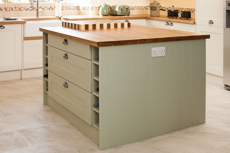 A roomy solid oak island with chunky butchers block chopping board is at the heart of this country kitchen in Lechlade. Finished in Farrow & Ball's warm and inviting 'Vert de Terre', with plenty of storage afforded by extra-wide drawers, flanked by storage space for up to 10 bottles of wine. http://www.josephkingsley.co.uk/solid-oak-kitchen-lechlade-case-study.html