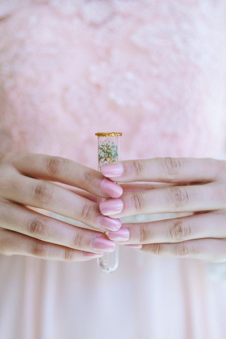 Lovely pink glass tube favours with glitter and baby's breath. Pink wedding nails, bridesmaid dress in pink.