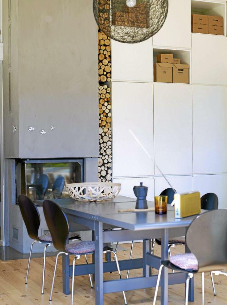 PEIS: En hel vegg er kledd med kjøkkenskap fra gulv til tak, fire meter i alt. Peisen Architektur-Kamin fra Brunner har heve- og senkedør, og bålet kan sees fra hele stuen. Mellom peisen og kjøkkenskapene er det spesiallaget hyller i metall som veden hviler på. Peisen er malt med organisk kalkmaling, Pure og Original fra wakeupliving.no, som ser ut som betong. Ifølge produsenten kan det være litt lurt å ta seg et par glass vin før en går i gang, for resultatet blir finest om en slurver litt…