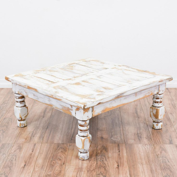 This shabby chic coffee table is featured in a solid wood with a distressed light wood and white chalk paint finish. This coffee table is in great condition with a square table top and carved spindle legs. Eclectic table perfect for a large living room! #shabbychic #tables #coffeetable #sandiegovintage #vintagefurniture