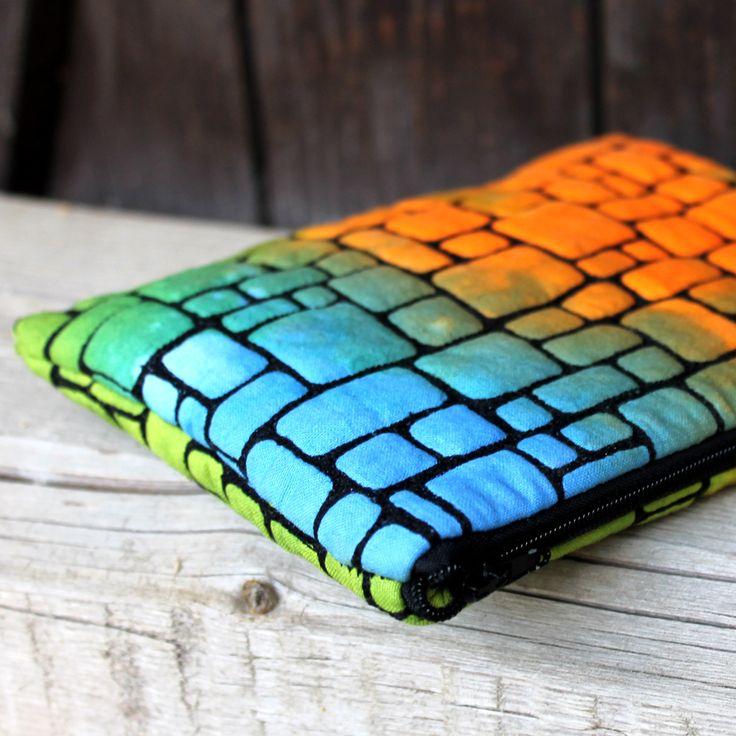 Taštička+barevná+Taštička+je+ušitá+z+ručně+barvené+látky,+na+které+se+objevuje+oranžová,+zelená+a+modrá.+Vnější+strana+taštičky+je+podložená+vatelínem+a+bavlněnou+látkou+a+všechny+tři+vrstvy+jsou+bohatě+vlastnoručně+proqiltované+(prošité)+černou+nití+v+několika+liních,+abych+dostala+vzor,+pro+který+byla+inspirací+zídka+pod+kostelem+ve+vedlejší+vesnici+....