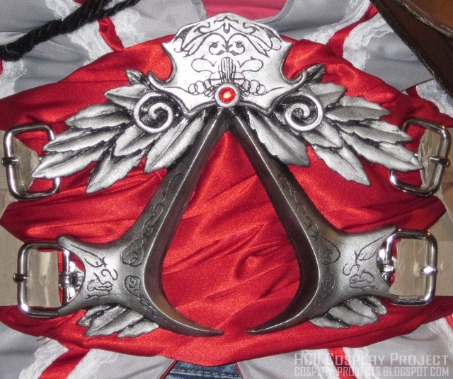 Hmm...very smart. The insignia is actually mounted on a plate that's bellow the red sash. As well as the buckles, which are also mounted on the plate to assure the insignia does not bear any actual stress. Hmm...