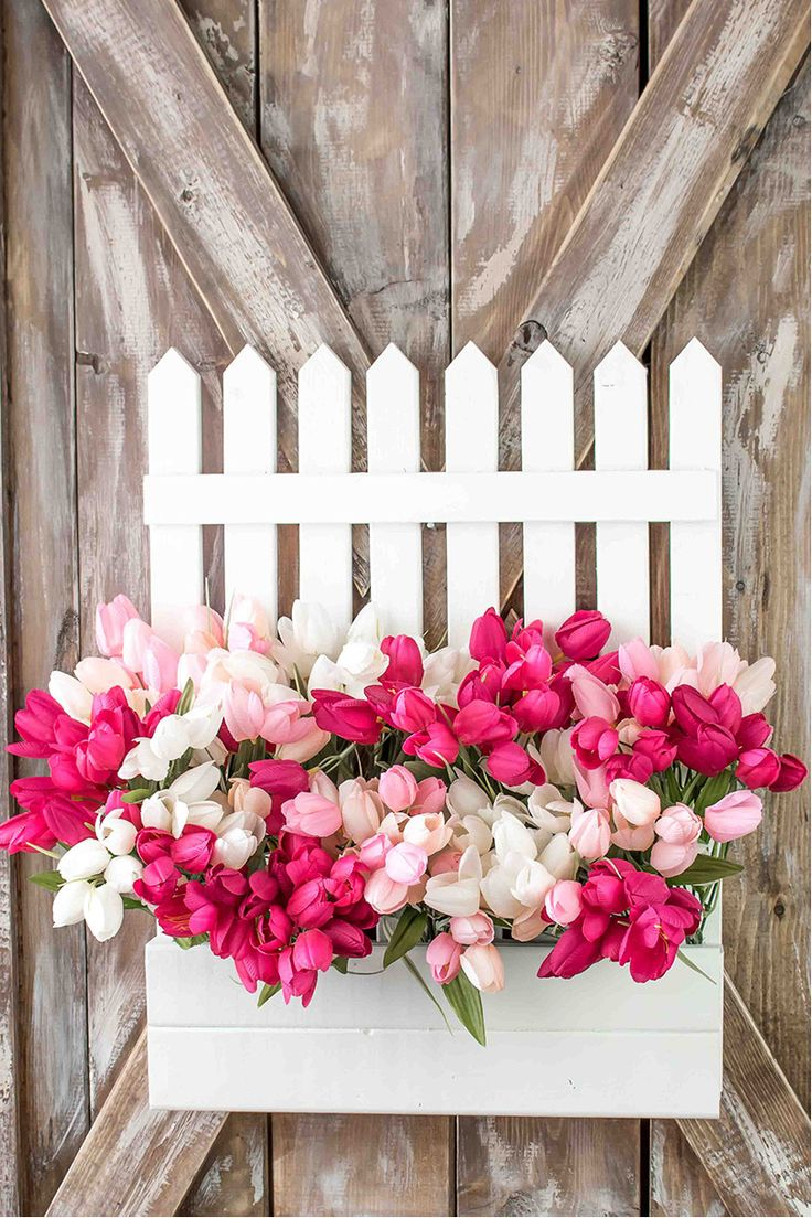 A fun DIY spring wreath that you can create in a few hours. A sweet white picket fence filled with flowers makes for a unique cottage style accent.