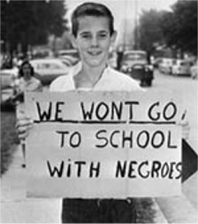 """This picture shows a young caucasian that is holding a poster saying """"We won't go to school with negroes."""" Because of the Jim Crow Laws these children are learning to be racist towards African Americans. -Chelsea Duran"""
