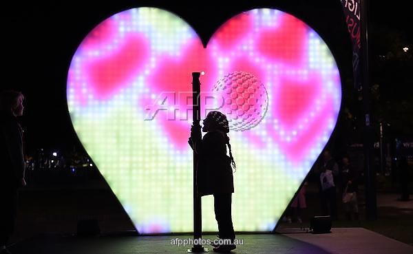 """A child shouts """"I love you"""" as a giant heart-shaped 'Love-O-Meter' is illuminated during the media preview of Vivid Sydney in Sydney on May 26, 2016 AFP PHOTO/ SAEED KHAN"""