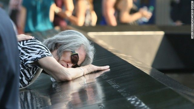 Mija Quigley of Princeton Junction, New Jersey, embraces the name of son Patrick Quigley at the 9/11 Memorial on September 11. He died aboard United Airlines Flight 175, which crashed into the World Trade Center on 9/11.