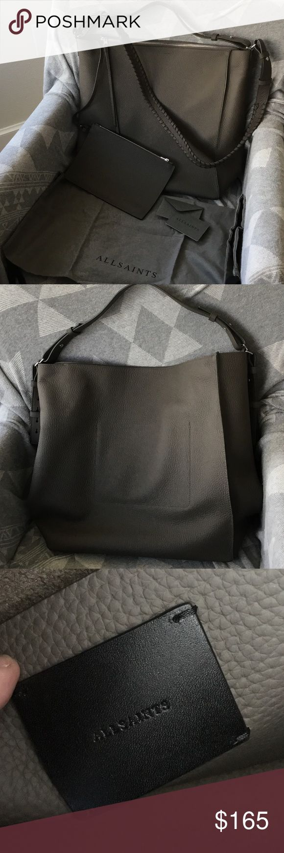 """EUC ALLSAINTS Kita North South Tote EUC ALLSAINTS Kita North South in Mink Grey. I bought this directly from the website, currently available for $348. Has two straps for multiple ways to carry, including crossbody. Both straps can be adjusted or removed. Also comes with a detachable pouch. Beautiful grained taupe grey leather that is super durable. Comes with dust bag and authenticity card. Measurements are 14"""" h, 13 1/4"""" w, 5 1/2"""" d. Used twice and realized it was to large for me. All…"""