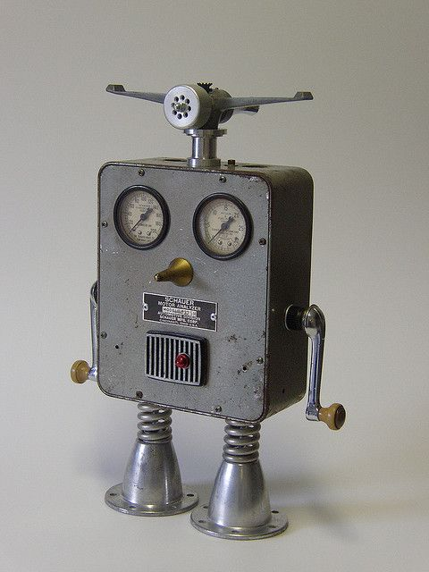"Schauer robot Schauer (15"") Wide-eyed and up for a challenge nothing gets past Schauer. Gloriously displaying his radar headgear (lawn sprinkler) and dual window cranks (arms) this bot is master of all he surveys. A vintage motor analyzer case, auto valve bodies, electric drill parts, springs and a big gold nose keep him on top of his game."