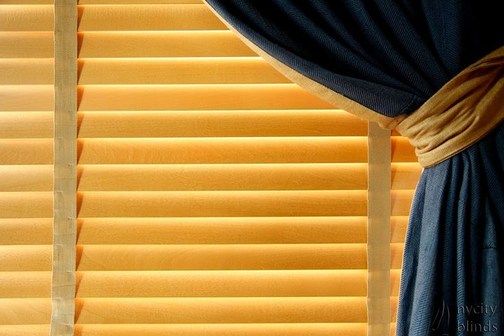 A blue curtain compliments 100% hardwood blinds by NY City Blinds.