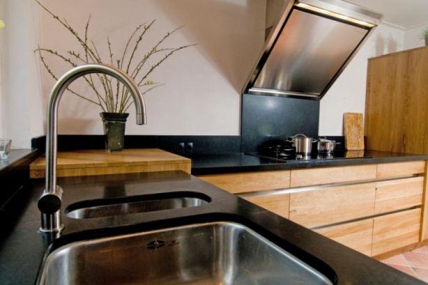 Natuurlijk modern  Moderne greeploze keuken met natuurlijke uitstraling door het gebruik van eiken hout. Door de in combinatie met het granietwerkblad en rvsgreeplijsten, RVS afzuiger andere details ontstaat er een moderne keuken met natuurlijke uitstraling.