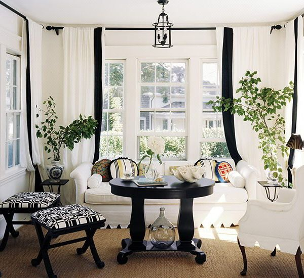 Great inspiration for lower-level porch. One day. A little too fussy for that, but like the black motif and white along with the seagrass rug.