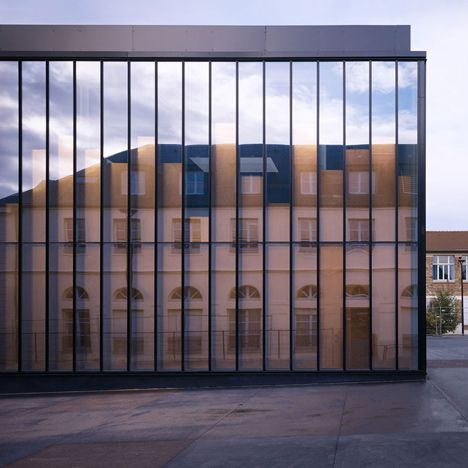 Copper-clad panels behind the glazed facade of this gymnasium.