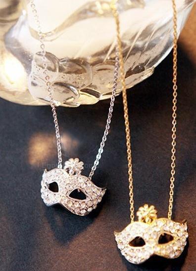 Maskesmykke  Kjempesøtt smykke formet som en maske, prydet med rhinestones.   Kr 49,-