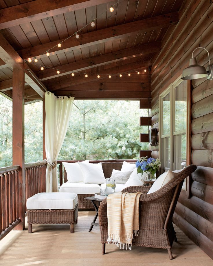 String lights twinkle over the front porch of this Ohio lake house, and wicker furniture surrounds an antique folding table.