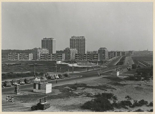 5-1959, Het witte gebouw midden rechts is de poffertjestent (als ik me goed herinner tevens indisch restaurant). De naam van de eigenaar is me ontschoten. Daarachter de schelpenstortplaats waar een schelpenvisser dagelijks zijn verzamelde schelpen kwam storten. Daarnaast moet dan nog een restant liggen van de oude tankgracht, destijds voor ons kinderen een prachtig speelterrein waar op stekeltjes werd gevist en waar vlotten werden gebouwd, van planken, gejat uit naburige bouwerijen.'  De…