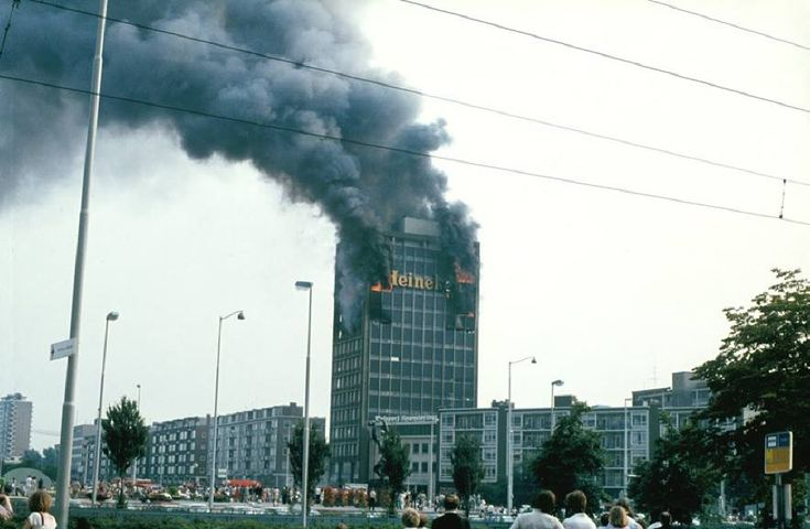 De Schiedamsedijk met Leuveflat in brand, 28/6/1978. De bovenste verdiepingen van de Leuveflat werd in de as gelegd. ,,Gelukkig vielen er geen slachtoffers. De hele Schiedamsedijk was afgezet, de witte overhemden van de politieagenten waren zwart van het roet. De ruiten sloegen eruit, luxaflex hing over de bovenleiding van de tram en de brandslangen die naar binnen gingen, waren op vele plaatsen lek door het glas dat erop was gevallen.