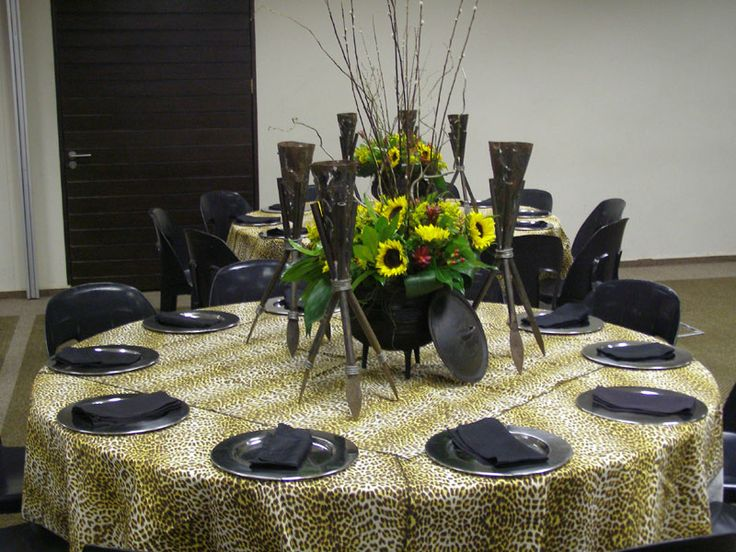 Zulu themed table with leopard print overlays, black three legged pot filled with sunflowers and assegai stands