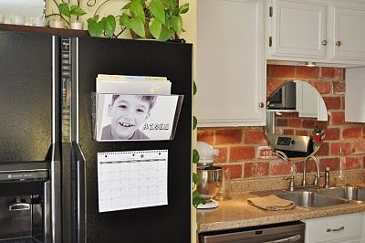 acrylic wall pocket on the fridge to organize papers for each kid.  Personalize it with pic of each kid.