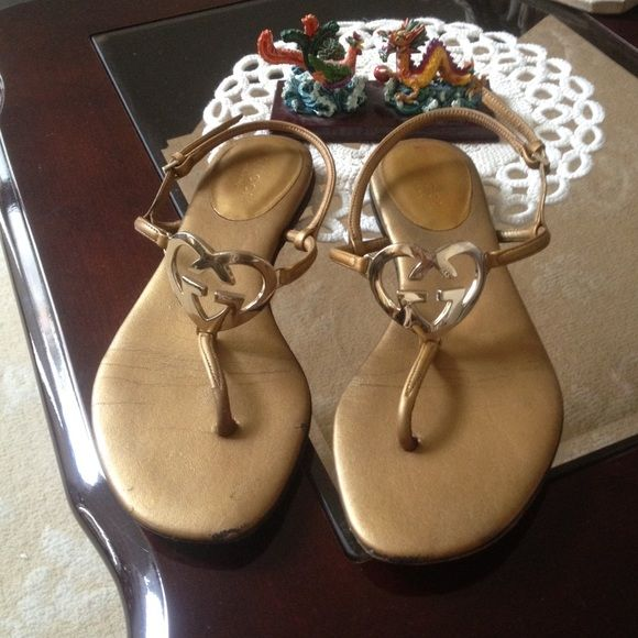 GUCCI Heart Shaped GG, Gold Flat Sandal These authentic Gucci sandals are adorable.  They're used but definitely still has a lot of life.  The heart shaped GG are radiant and very unique.  Perfect to slide on with anything in the summer.   ❤️ Gucci Shoes Sandals