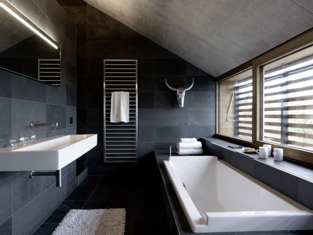 un carrelage mural et de sol en gris foncé et une baignoire blanche