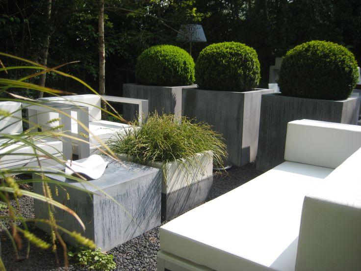 Gandia Blasco met zinken blokken als tafeltje en grote zinken bakken met Buxus als afscheiding.