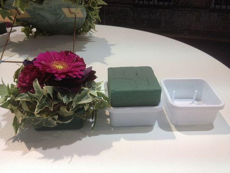 Die weiße Schale wird mit Steckschaum für Frischblumen ausgestattet. Die Steckmasse wird mit einem Messer auf die gewünschte Größe geschnitten. Wässern , stecken , fertig ist die Blumendeko.
