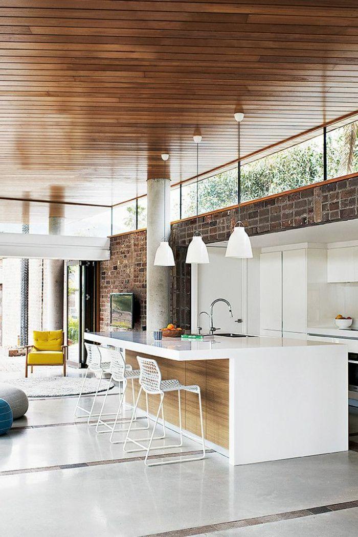 drei weiße lampen in einer großen küche mit kochinsel