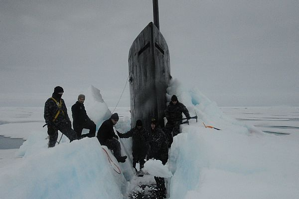 Sailors aboard the fast attack submarine USS Seawolf (SSN 21) remove Arctic ice from the hull after surfacing at the North Pole.