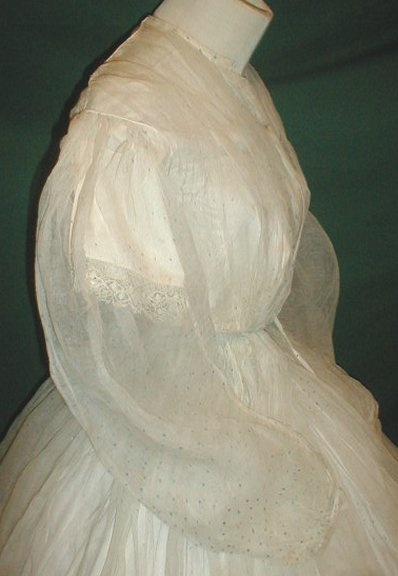 "Gossamer 1860's two piece gauze dress, de-accessioned from NY city museum. Fabric has scattered tiny aqua blue dot pattern. Bodice line with cotton camisole that has short lace trimmed sleeves & front hook & eye closure. Neck, shoulders, armscyes are piped. Skirt unlined. Bust: 30""; Waist: 22""; skirt length: 43""; width at hem: 174""."