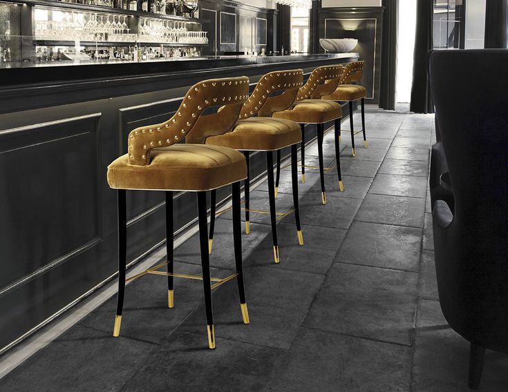 Kelly bar chair dazzles in its smooth mustard velvet and long, elegant legs. The glossy black structure, finished with a delicate touch of gold, complements the polished brass nails that adorn the contours of the graceful backrest.