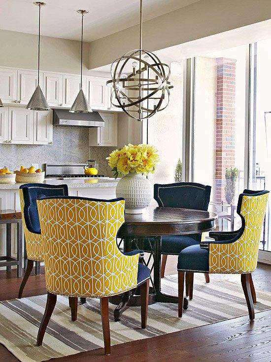 Even if your dining room is just a space off the kitchen, don't be afraid to give it sophisticated style. In this dining space, handsome, substantial furniture and colors set the space apart and make it stand out against the simple white kitchen. The bold yellow print on the back of the chairs contrasts the navy cushions and is a burst of color against the dark wood floor and white walls./