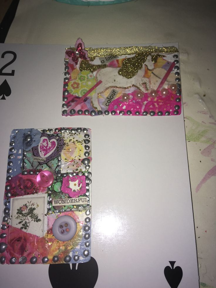 Regular sized cards decorated laying on very large playing card