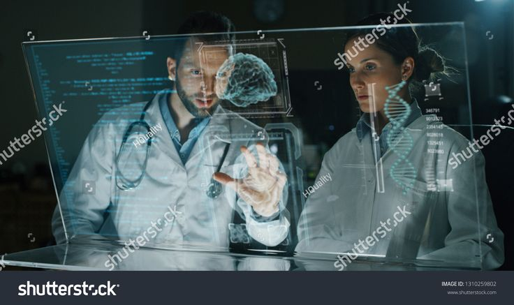 Portrait of futuristic scientists doctors using augmented reality screen with hologram graphics for viewing results of DNA research in laboratory.Conc…